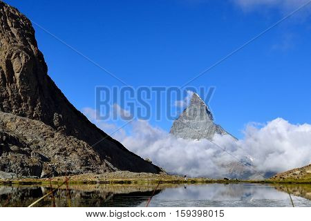 The woman hiking to Riffelsee lake in front of Matterhorn and cloud during summer Zermatt Switzerland.