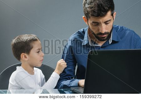 Father On Laptop Ignoring Son While The Child Tries To Catch His Attention.