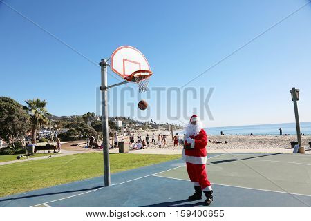 Santa Claus plays Basket Ball outside. Santa shoots and scores while playing basket ball.