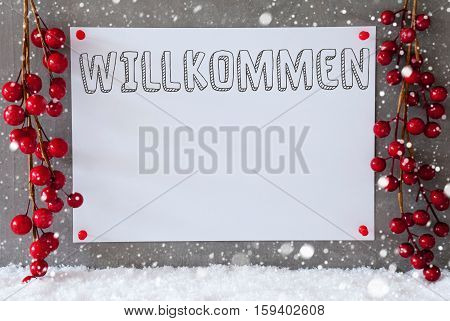 Label With German Text Willkommen Means Welcome. Red Christmas Decoration On Snow. Urban And Modern Cement Wall As Background With Snowflakes.