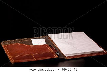 Expensive Leather portfolio with writing pad and pen on black background