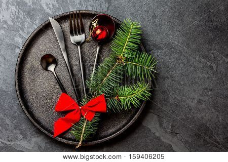 Black cutlery set with Christmas decoration - fir tree brunch on black iron plate on black slate background. Copy space, top view. Christmas menu background