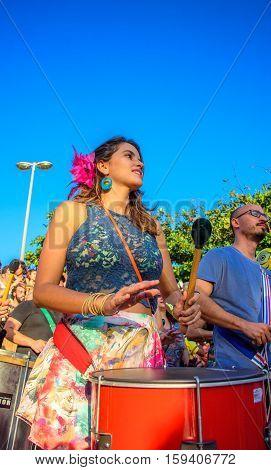 27 November, 2016. Beautiful woman playing batucada in the street at sunny day at Festival Fanfare Activist Festival de Fanfarras Ativistas - HONK RiO 2016 at Leme district, Rio de Janeiro, Brazil