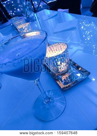 Blue Martini on candlelight table winter wonderland theme happy hour drinks. Celebration for the end of the year, fancy cocktails, New Years eve party, cocktails or Christmas