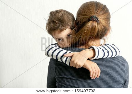 Mother hugging cute little boy, on light background