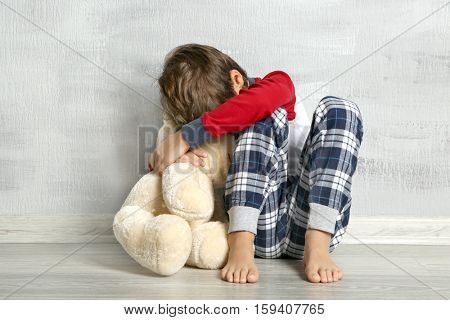 Sad little boy with teddy bear sitting on floor in empty room