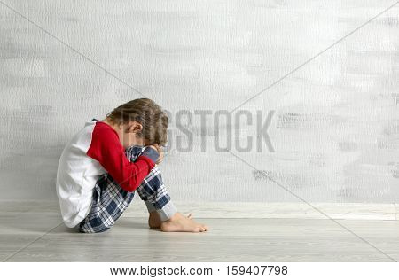 Sad little boy sitting on floor in empty room
