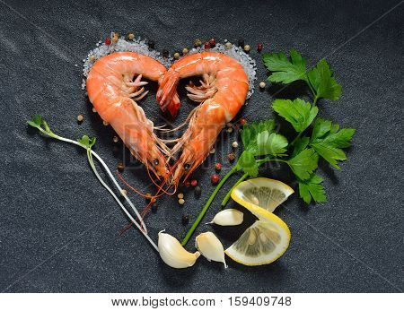 Cooked shrimps prawns heart shape with seasonings on stone background