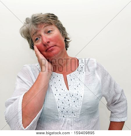 Woman shocked by extent of sun burn. Very Tanned Woman. White background