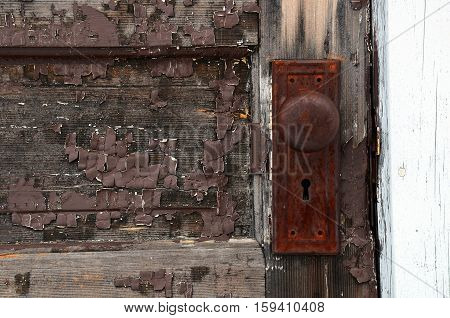 An abstract image of an old vintage door handle on an old wooden door with peeling brown paint.