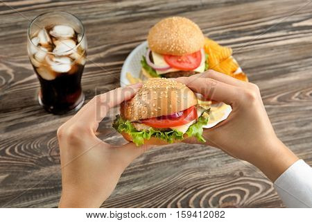Woman eating tasty burger with coke in kitchen