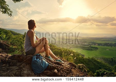 A girl sits on the edge of the cliff and looking at the sun valley and mountains