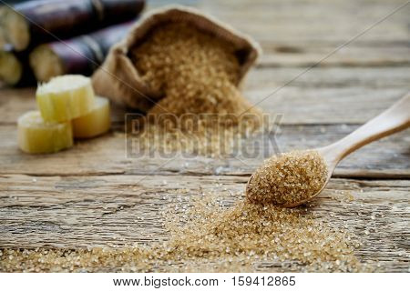 Sugar in wooden spoon with sugar in burlap sack sugarcane on wooden desk. Sugar crystals closeup. Soft focus(selective focus).