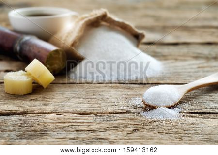Sugar in burlap sack with sugarcane and white cup of coffee on wooden background. Full bag of sugar crystals closeup.soft focus(selective focus)