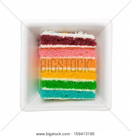 Slice of rainbow cake in a square bowl isolated on white background