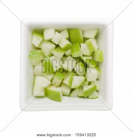 Diced green apple in a square bowl isolated on white background