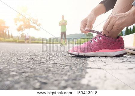 Barefoot running shoes closeup. Female athlete tying laces for jogging on road in minimalistic barefoot running shoes. Runner getting ready for training. Sport lifestyle.