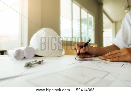 Hands of engineer working on blueprint with engineering tools and safety helmet on desk. Construction concept. Vintage tone retro filter effectsoft focus(selective focus).