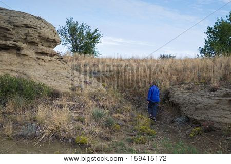 Woman wearing a cornflower blue fleece jacket with her back to the camera hiking on a path through sandstone rock formations with blue sky and thin clouds above. Photographed in natural light at Swords Park, Billings, Montana