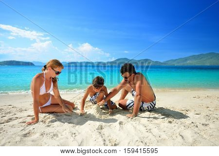 Happy family relaxing on the beach on a background of the islands.
