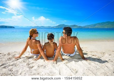 Happy family sunning on the beach on the background of the islands.