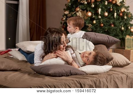Happy family are lying on a bed near Christmas tree at home. Merry Christmas and Happy New Year. Beautiful young mother with two sons.