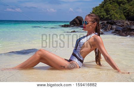 Sensual brunette woman in elegant swimsuit sitting in the water on sandy beach by the rocks over beautiful lagoon sea, blue sky and tropical island background