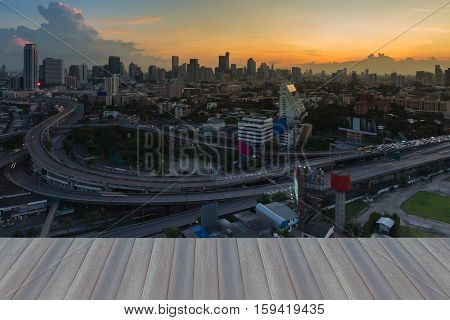Opening wooden floor, Aerial view highway interchanged with city downtown background during sunset time