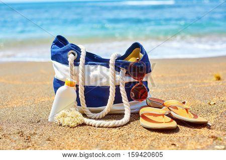 Beach Bag, Flip Flops And Sunscreen On Beach