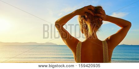 A back side view on a wonderful young woman watching to sea and raising her hands on sunrise.Panoramic view