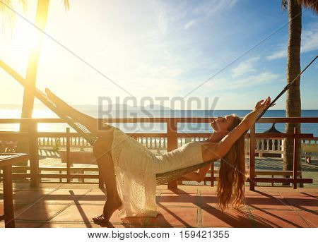 solitude woman lie alone in hammock at sunset day on the beach. Summer vacation concept