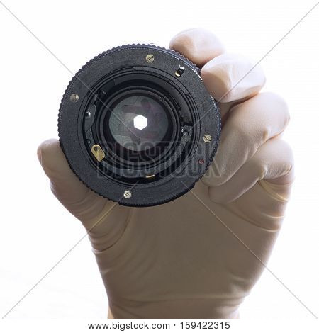 Hand and lens, front view. Lens camera in his hand, a hand in a white glove on a white background