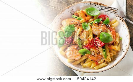 Penne Pasta With Shrimp, Tomatoes And Herbs On A Old Wooden Table.