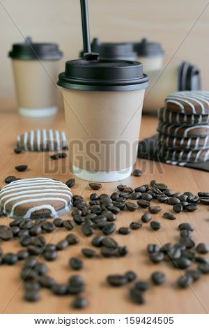 Paper coffee glass cookies and grains of coffee on a table