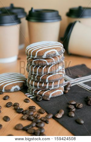 Cookies paper coffee glasses and grains of coffee on a table