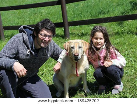young father with his little girl and the labrador dog