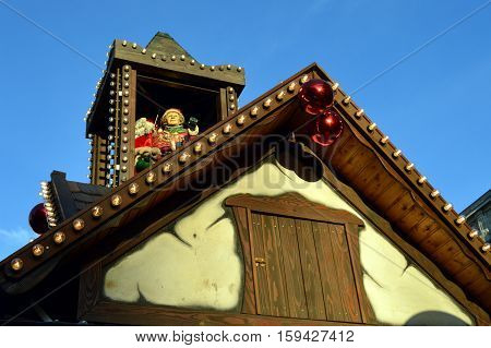 Mom and papa christmas on a wooden tower on a cottage