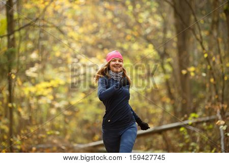 Beautiful sporty young woman jogging in autumn forest