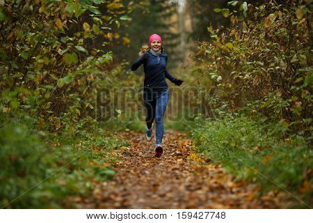 Young sportswoman running among trees