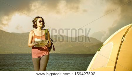 Young woman tourist walks on the seashore reading the map. Traveling along Asia freedom and active lifestyle concept