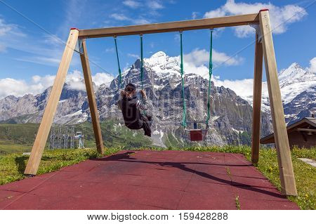 young woman on a swing swinging over the mountains Grindelwald Switzerland
