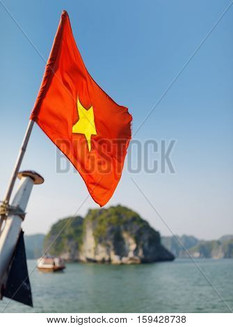Closeup view of the flag of Vietnam (red flag with a gold star) fluttering on blue sky background in the Halong Bay at the Gulf of Tonkin of the South China Sea Vietnam.