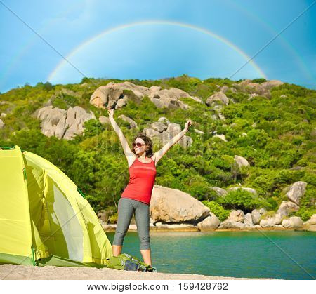 Portrait of happy traveler girl with raised up hands enjoying rainbow view mountains landscape. Travel to Asia happiness emotion summer holiday concept