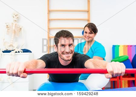 Young man working out in physical therapy on swiss ball with gymnastic stick