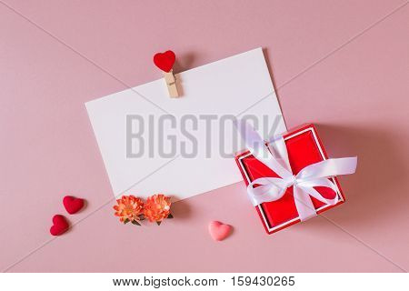 Valentine day composition: red gift box with bow stationery / photo template with clamp small hearts and spring flowers on light pink background. Top view.