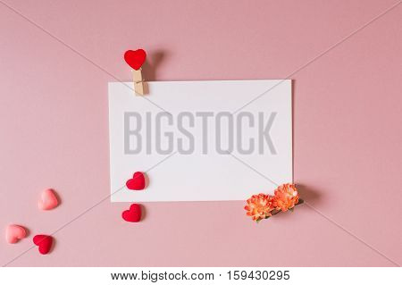 Valentine day composition: stationery / photo template with clamp spring flowers and small hearts on light pink background. Top view.