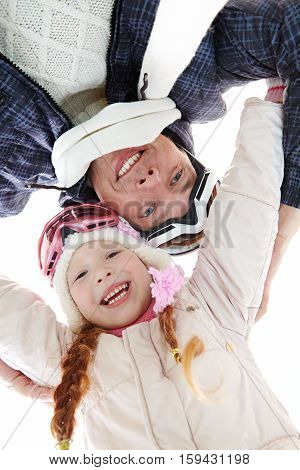 Directly below view of cheerful father and daughter wearing ski goggles