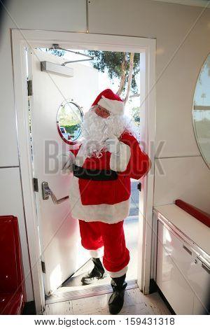 Santa Claus enters through a doorway. Cute santa claus concepts.