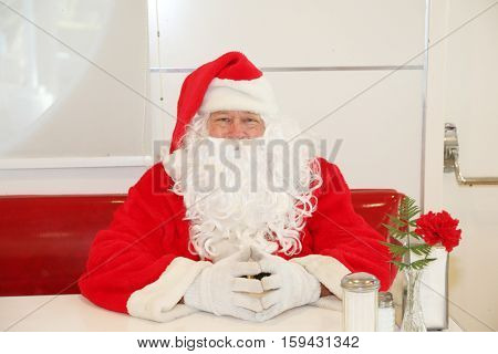 Santa Claus sits in a restaurant or diner. Cute Santa Claus concepts.