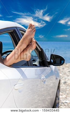 Woman's legs dangling out a car window